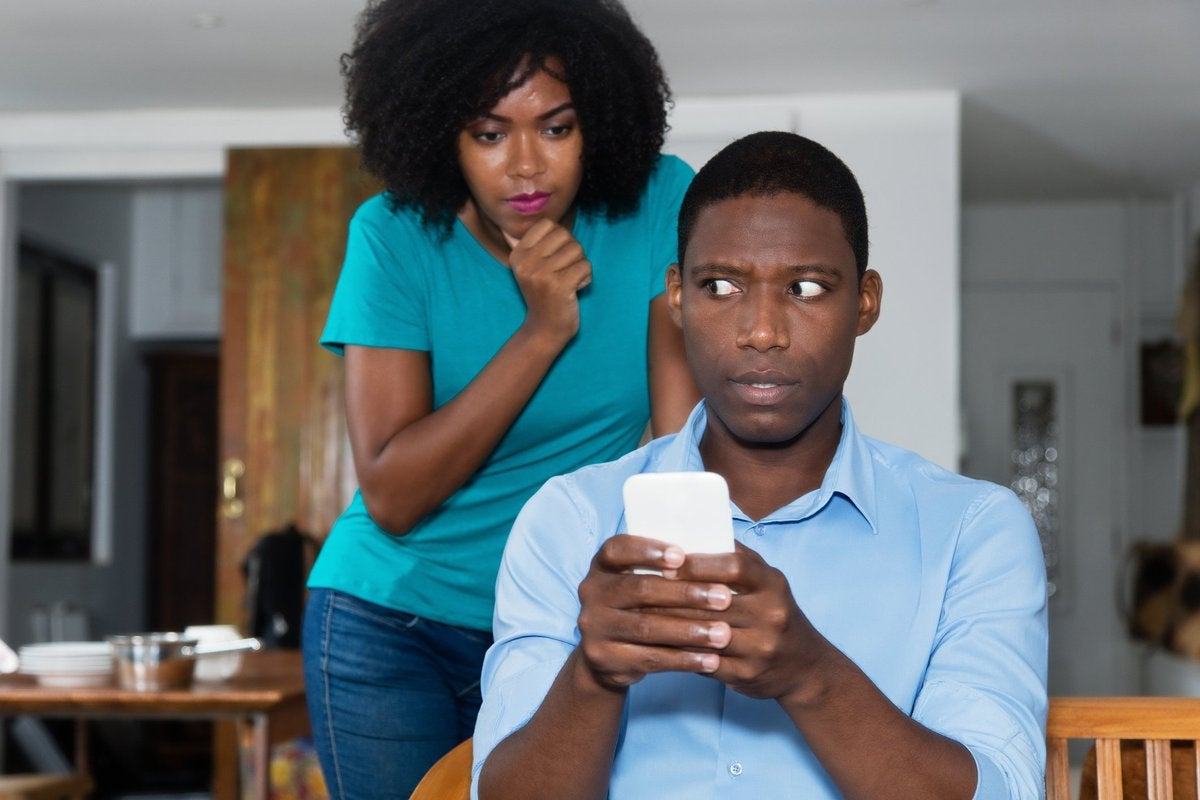 Woman looking over scared man's shoulder at his phone.