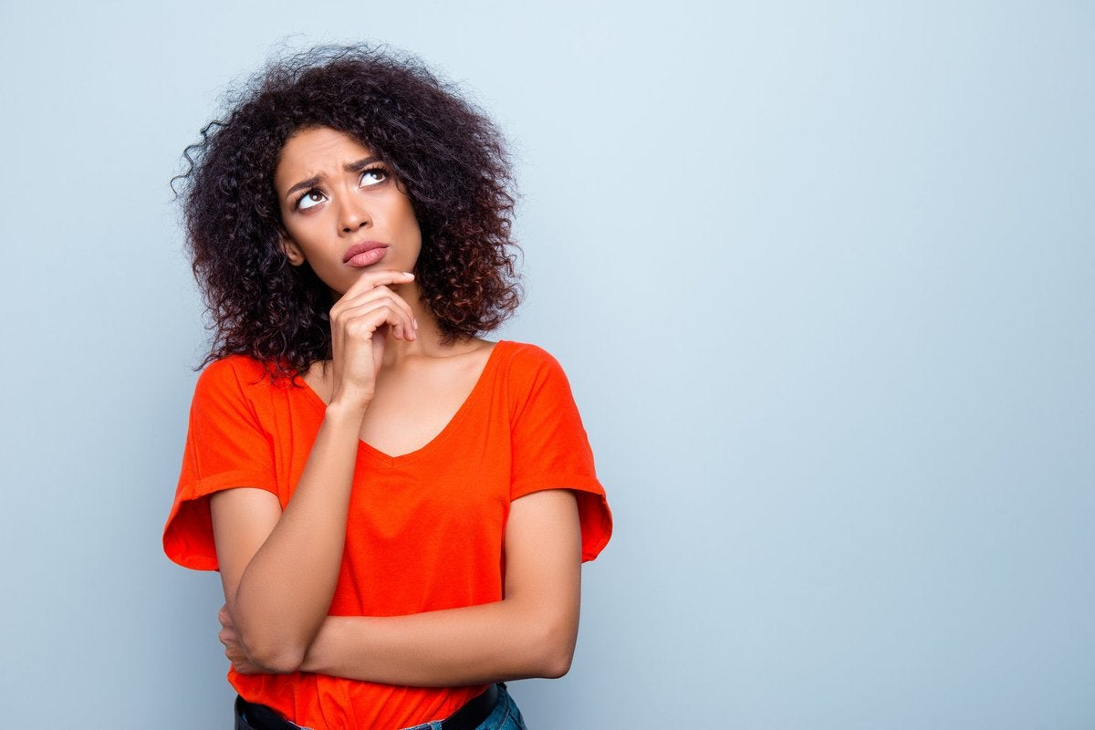 Woman standing with hand on chin contemplating her decision.
