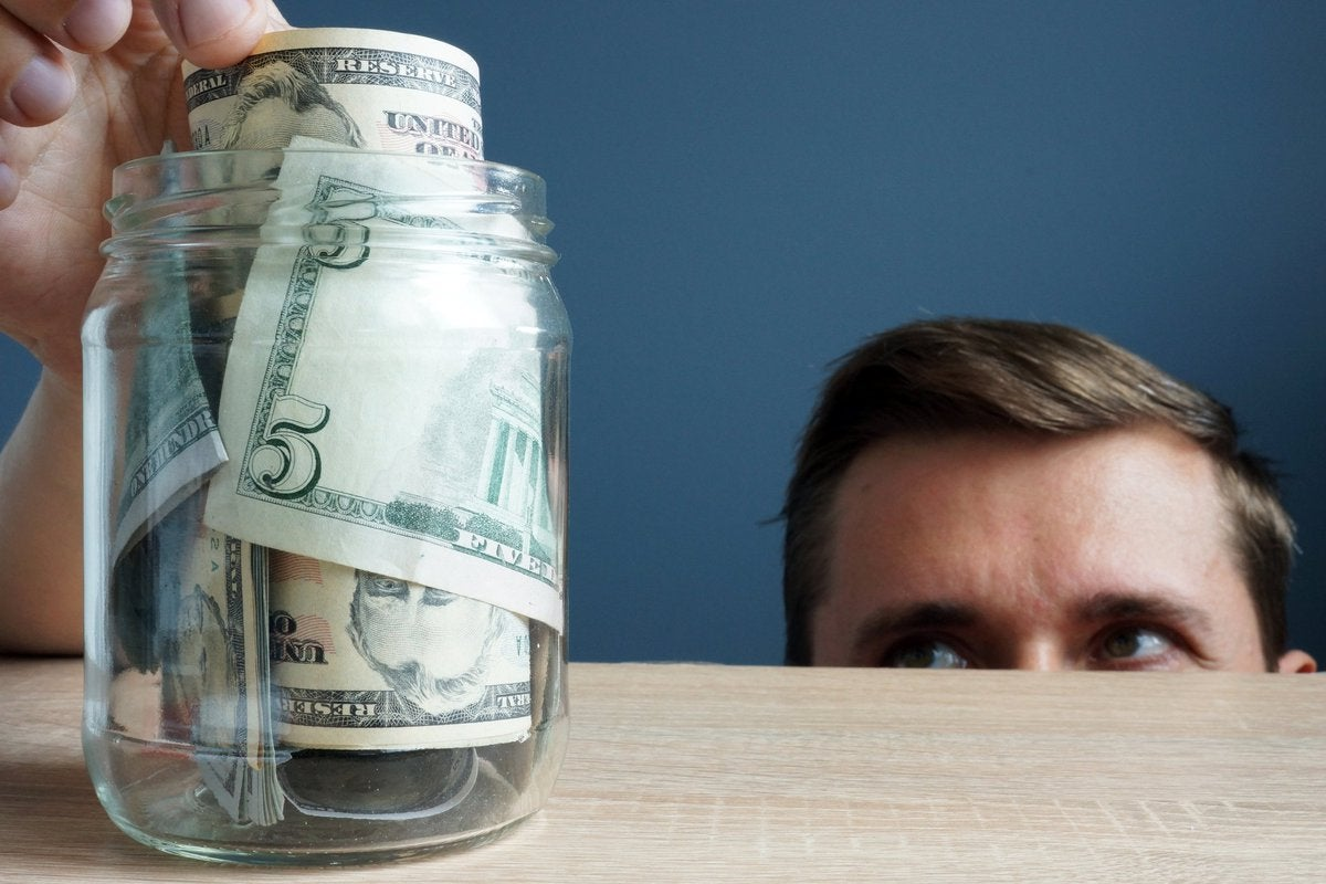 Half of man's face peering up over a counter as he sneaks a five-dollar bill out of a jar full of money.