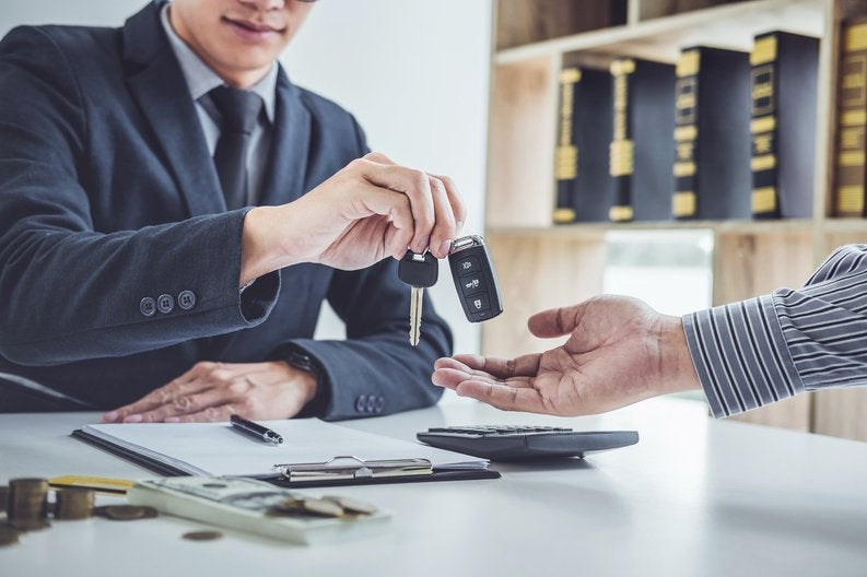 Man in suit reaching across desk to drop car keys into other person's hand.