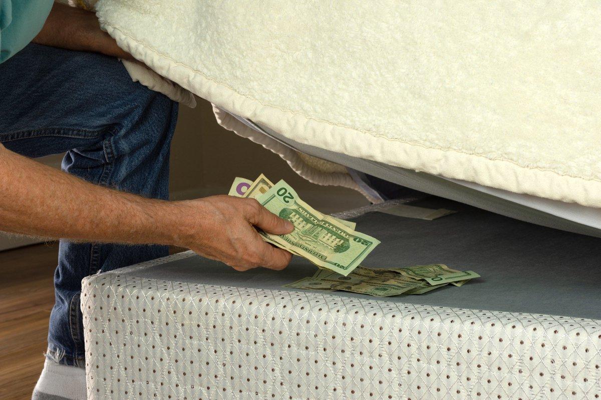 Man's arm hiding wad of cash under mattress.