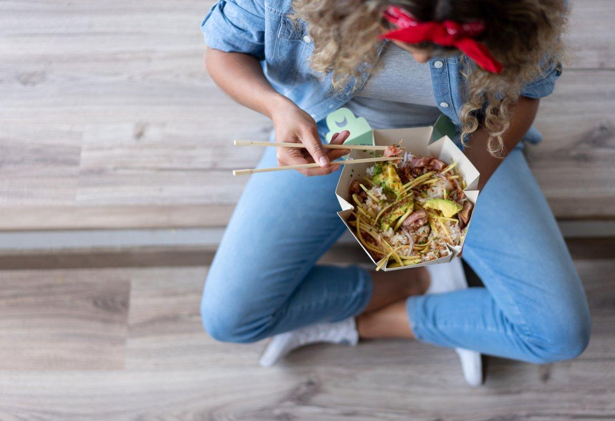 Crosslegged woman eats takeout with chopsticks.