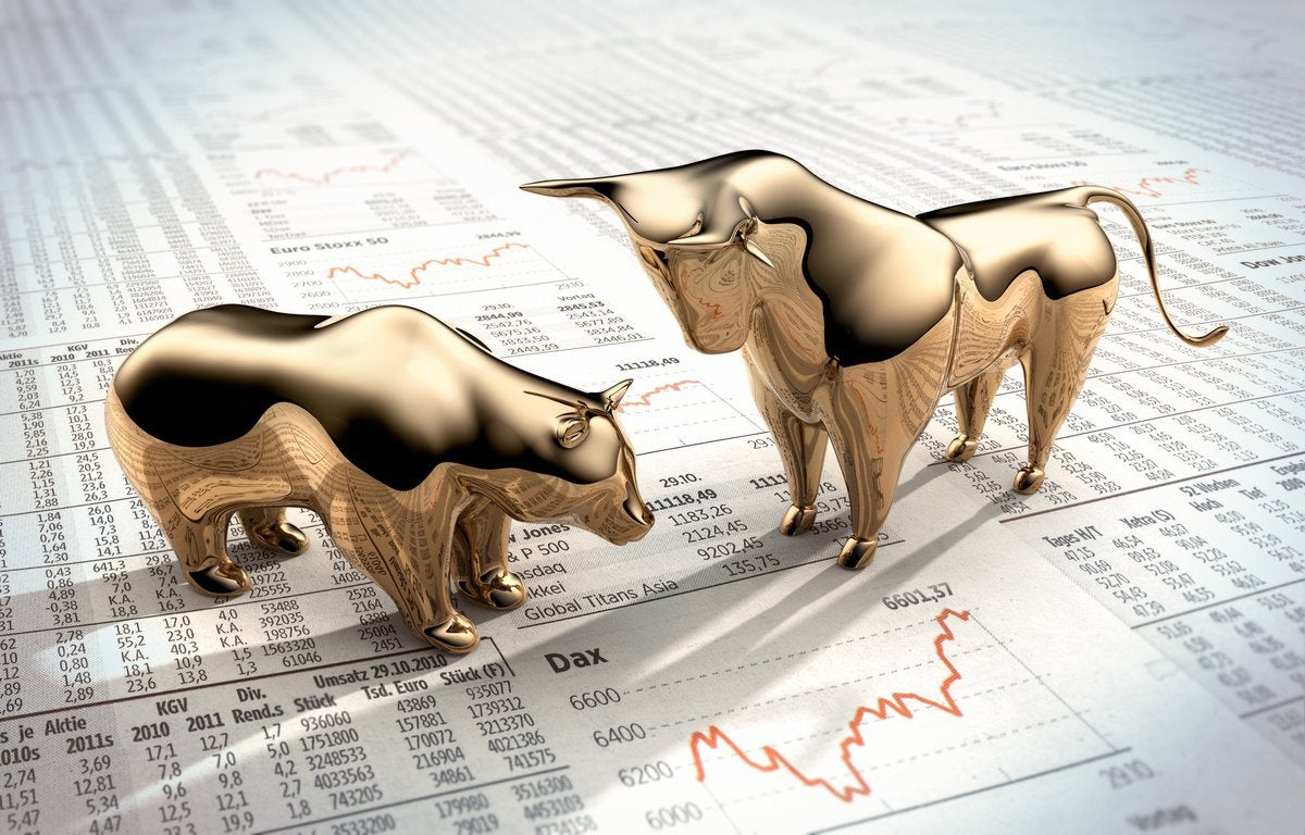 A gold bull and bear figurines on stock market papers.