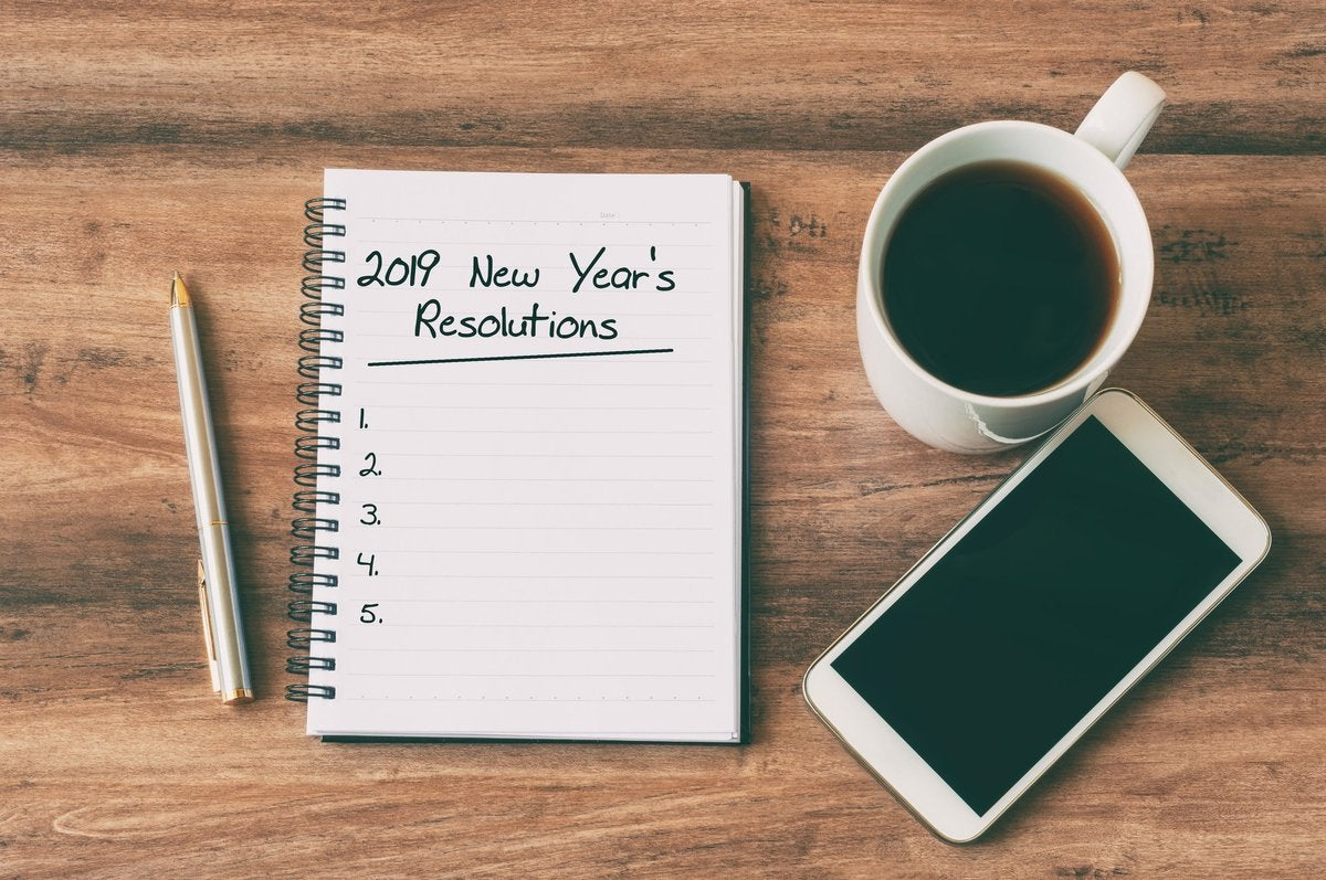 Cup of coffee, smartphone, pen, and notepad for 2019 New Year's Resolutions.