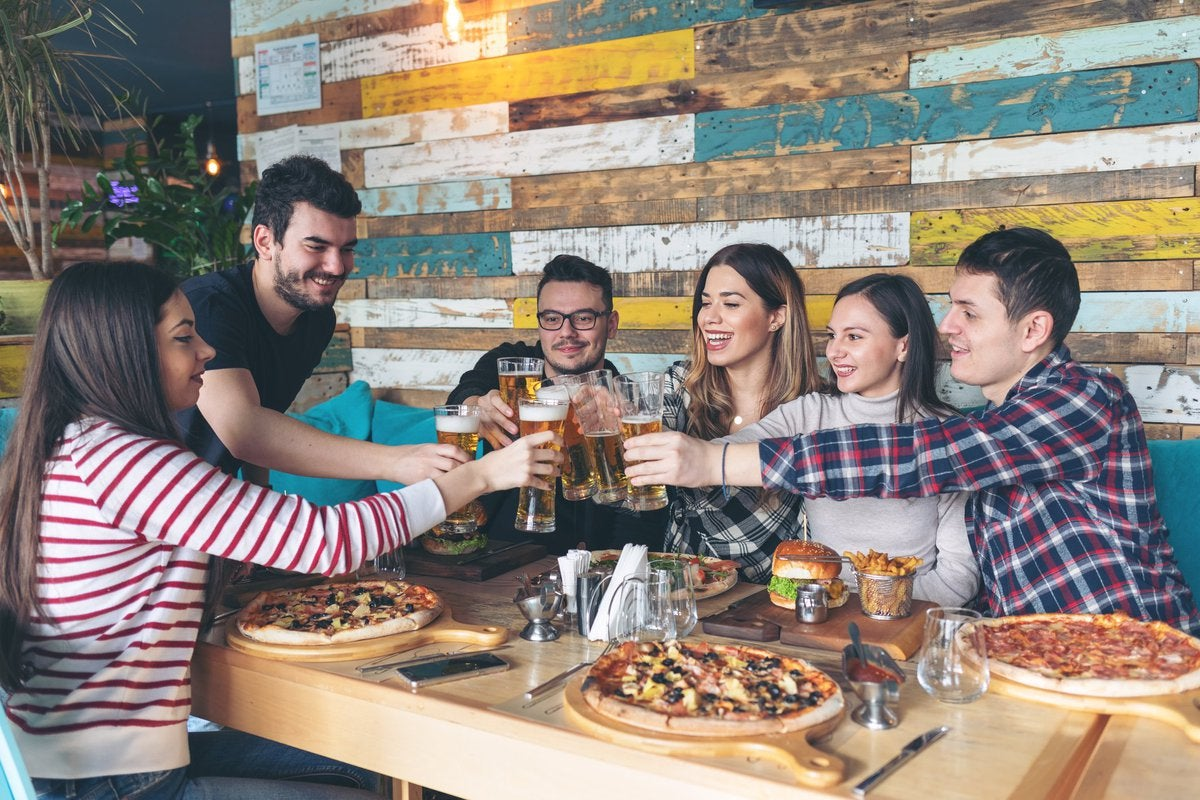 A group of friends at a restaurant enjoying pizza and beer.