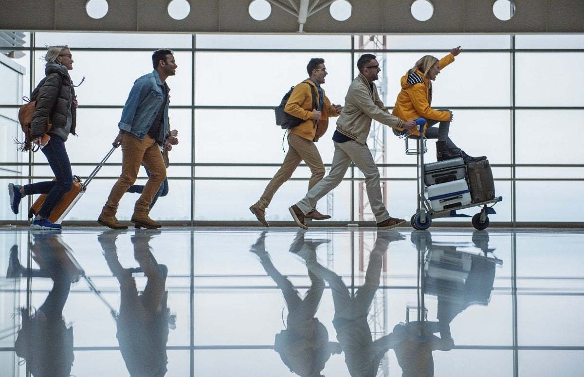 A group of friends racing through an airport with their suitcases.