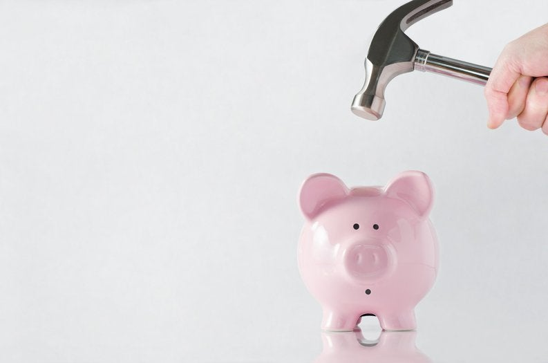 A hand holding a hammer over a worried-looking piggy bank.