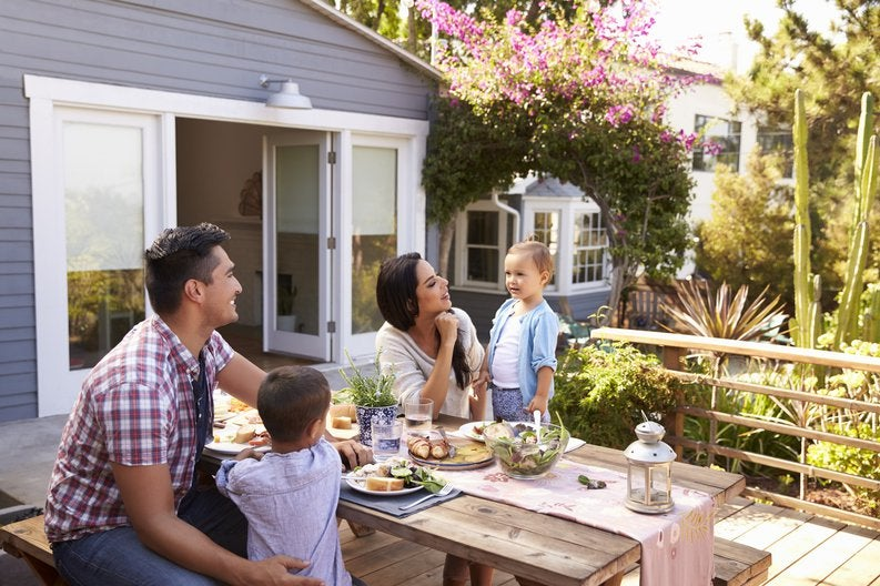 Two parents with their young children having lunch at a picnic table on their back deck.