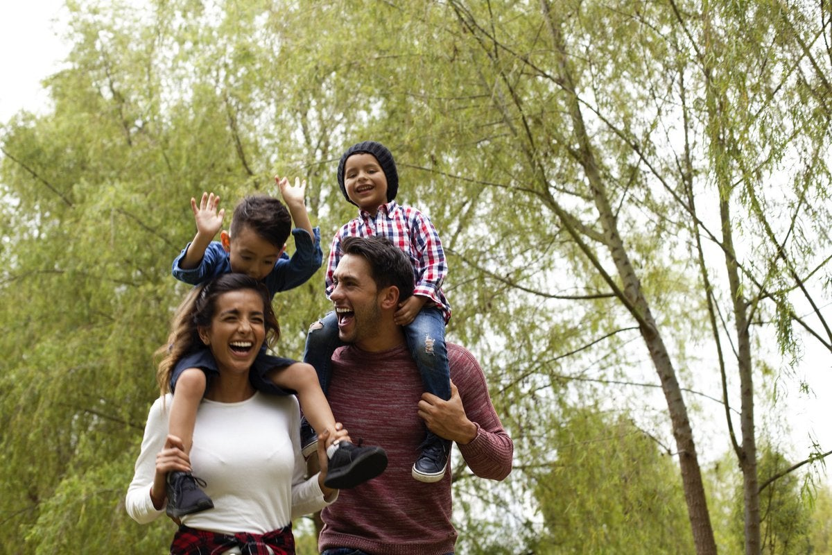 A happy family walking through a park with the young kids on the parents' shoulders.