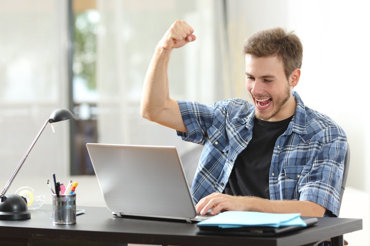 Happy man at laptop raises his fist in the air.