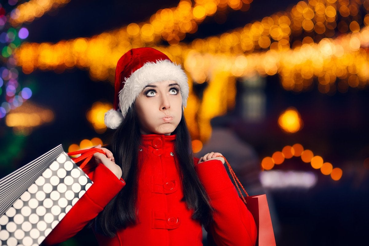 Woman in santa hat pursing her lips as she carries shopping bags.