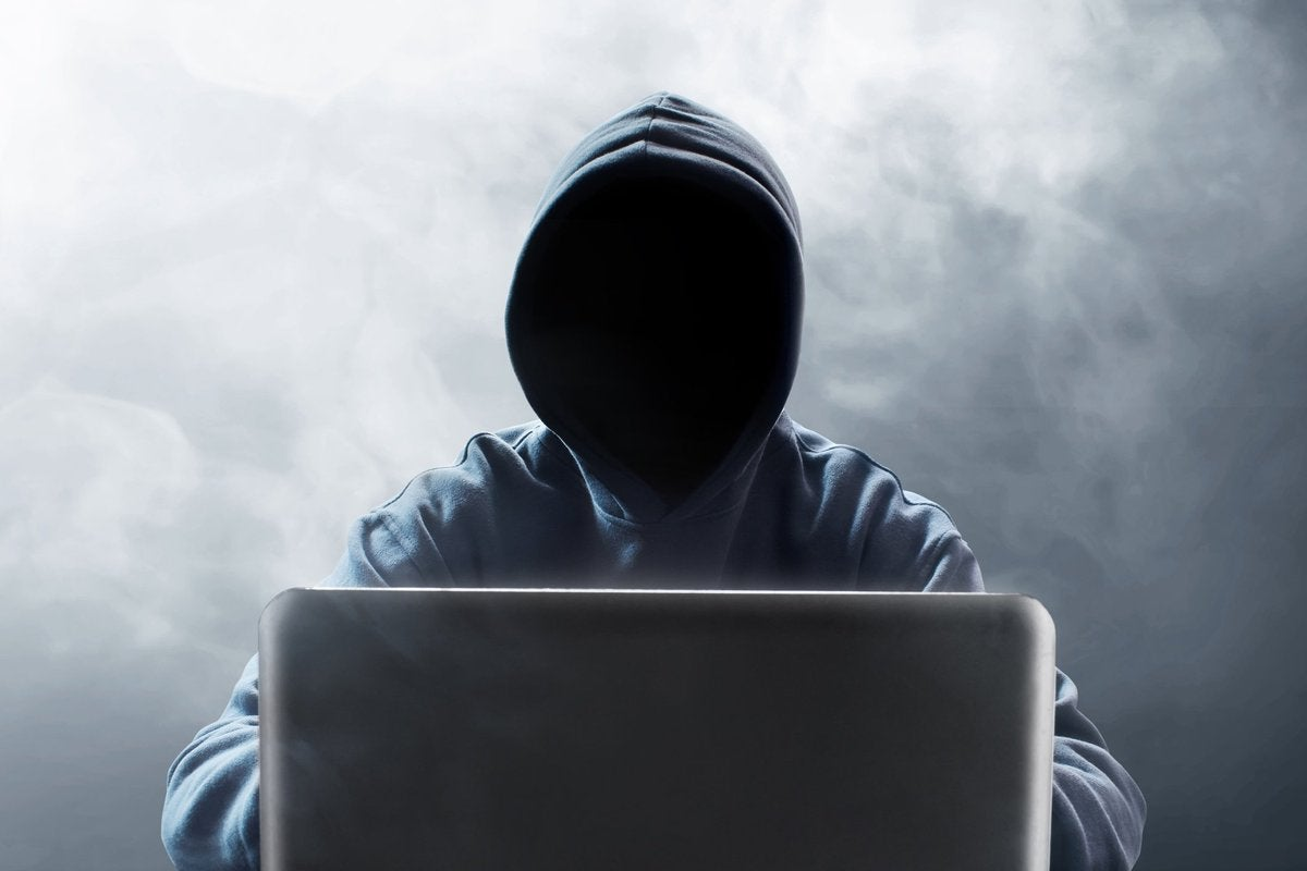 Hooded figure at laptop