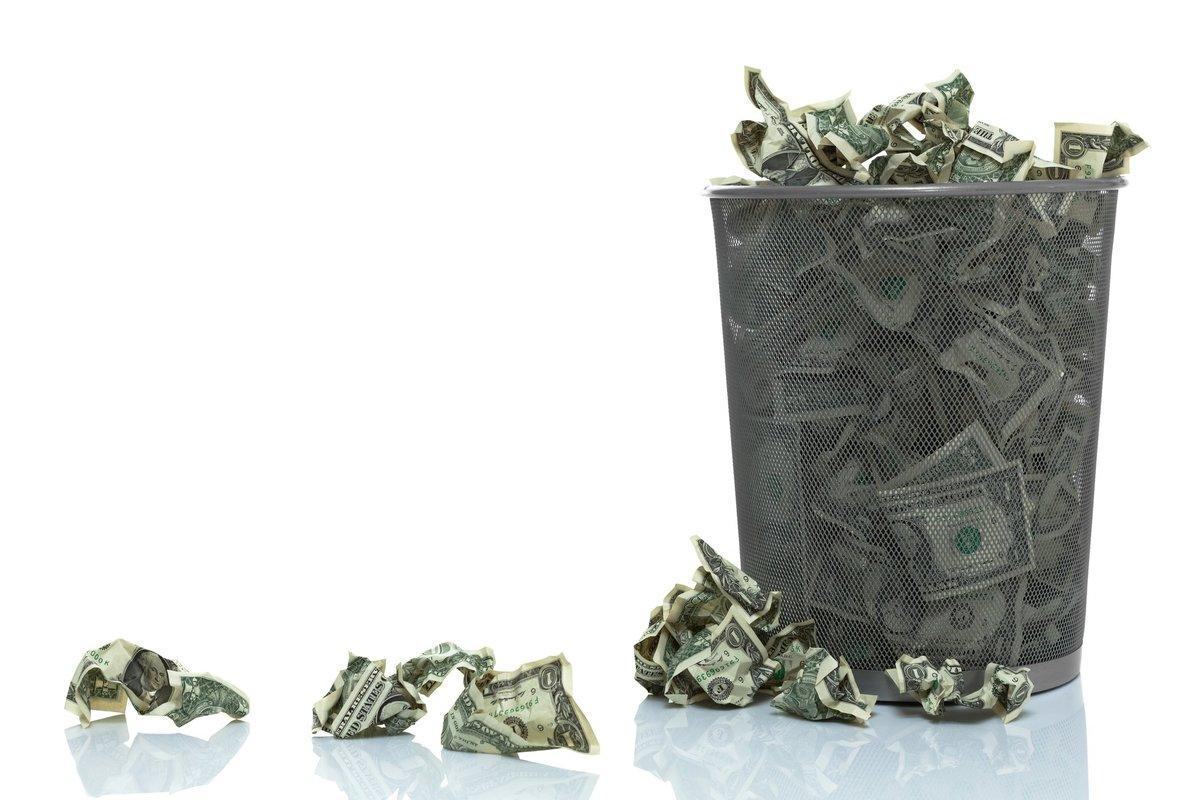 Trash can full of dollar bills.