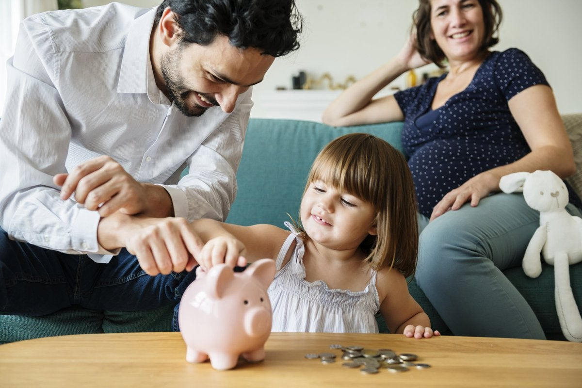 Happy Father Showing His Daughter How To Put Coins In Piggy Bank While Mom Watches