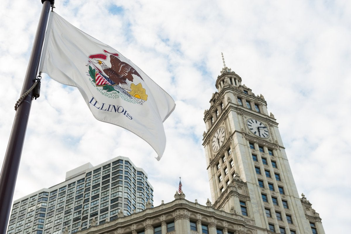 The Illinois state flag flying in front of buildings in Chicago.
