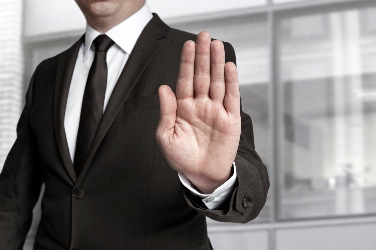 A man in business suit holds out his hand to indicate stop.