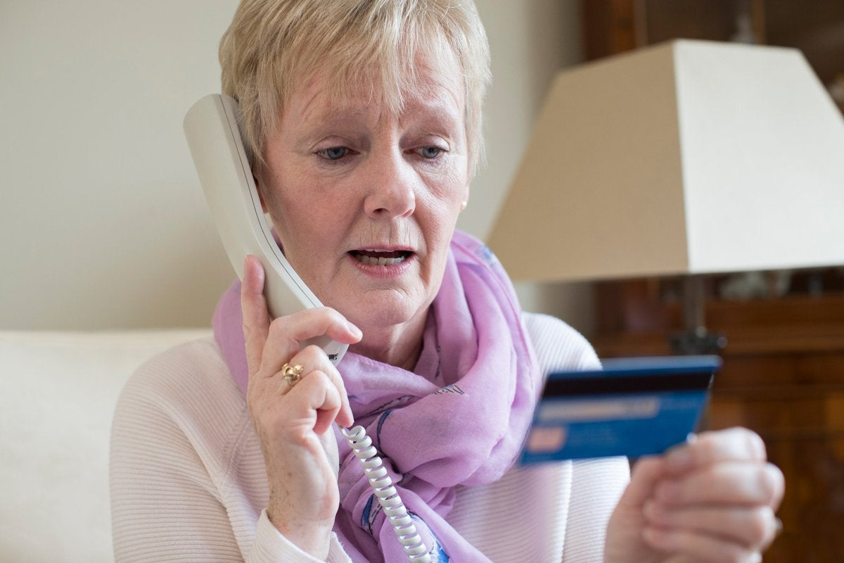 Concerned older woman looking at a credit card while on the phone.