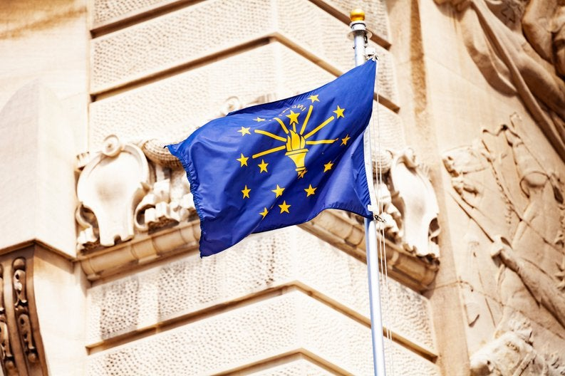 The Indiana state flag flying in front of a decorative building facade.
