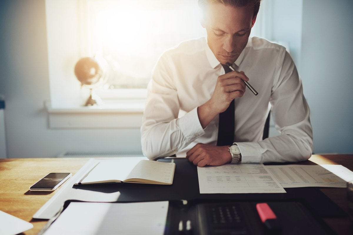 Man reading papers at a desk in a sunny office.