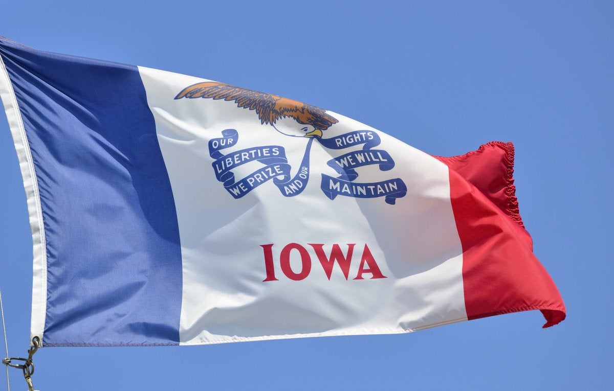 The Iowa state flag flying in front of a blue sky.