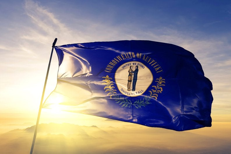 The Kentucky state flag flying in front of a sunny sky.