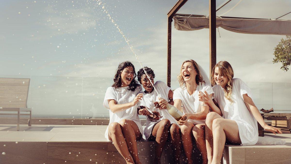 Four women popping bottle of champagne.