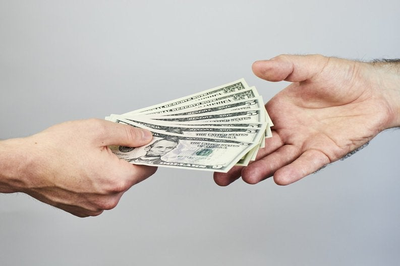 One hand holding cash and another hand reaching out to accept it.