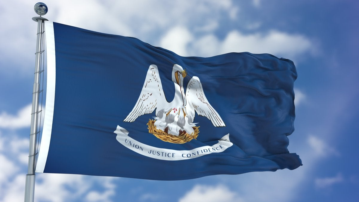The Louisiana state flag flying in front of a blue sky and white clouds.