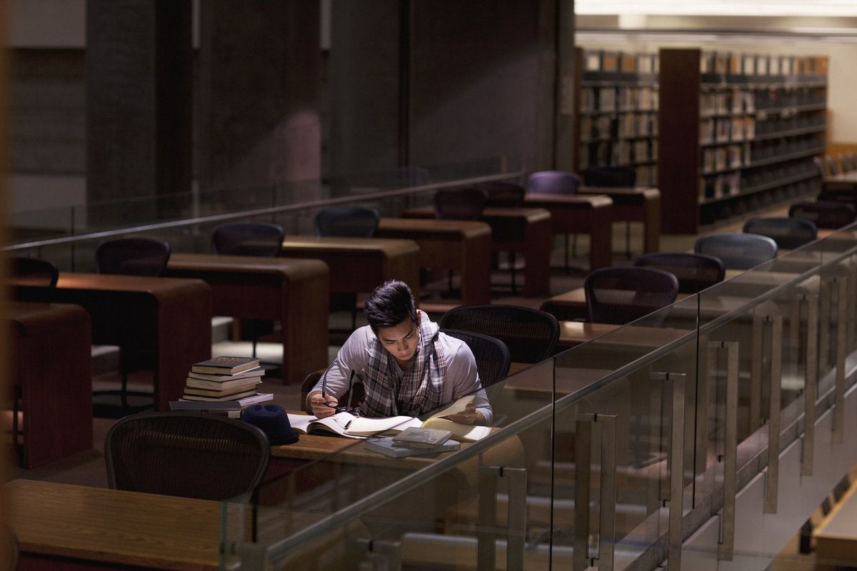 A male college student studying alone in a library.