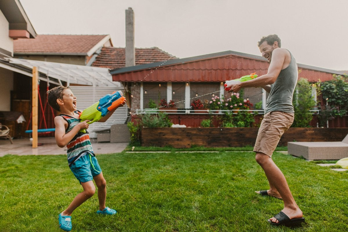 Man and child play with squirt guns in home's yard.