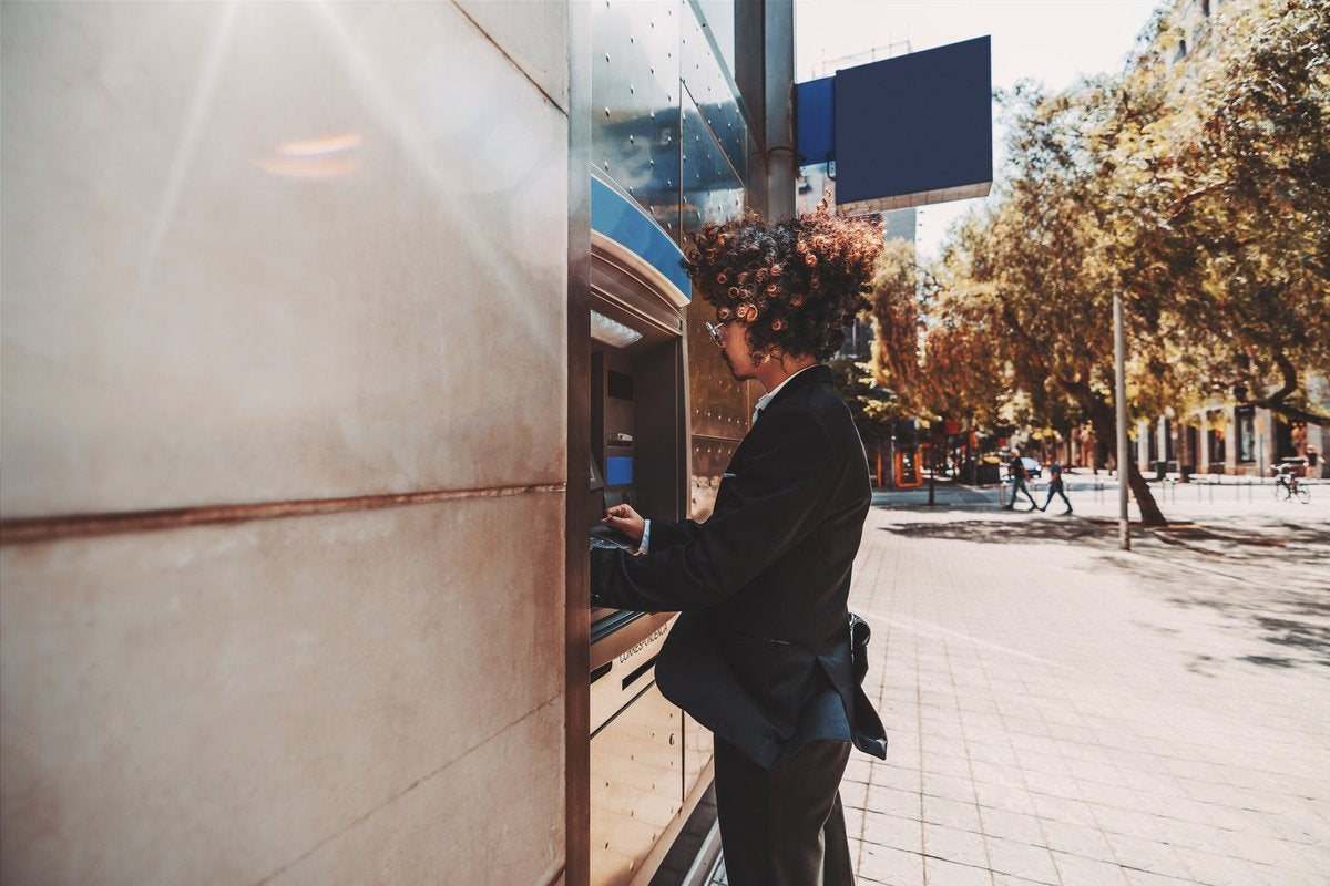 A young man in a suit using an outdoor ATM.
