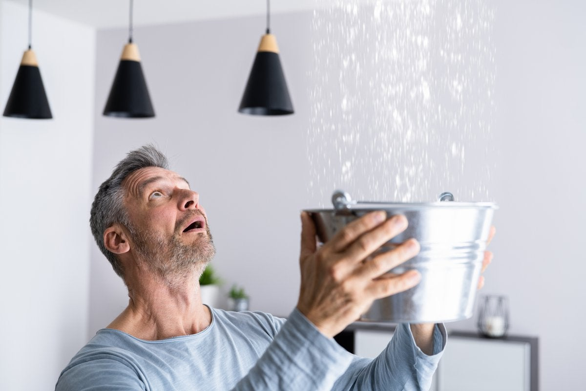 Man catching leaking water from ceiling in a bucket.