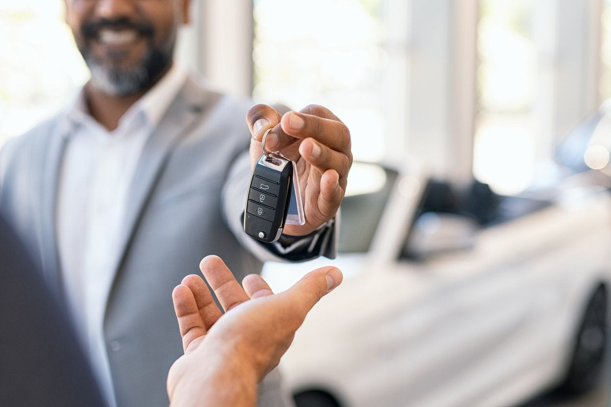A salesman handing over the keys to a new car.