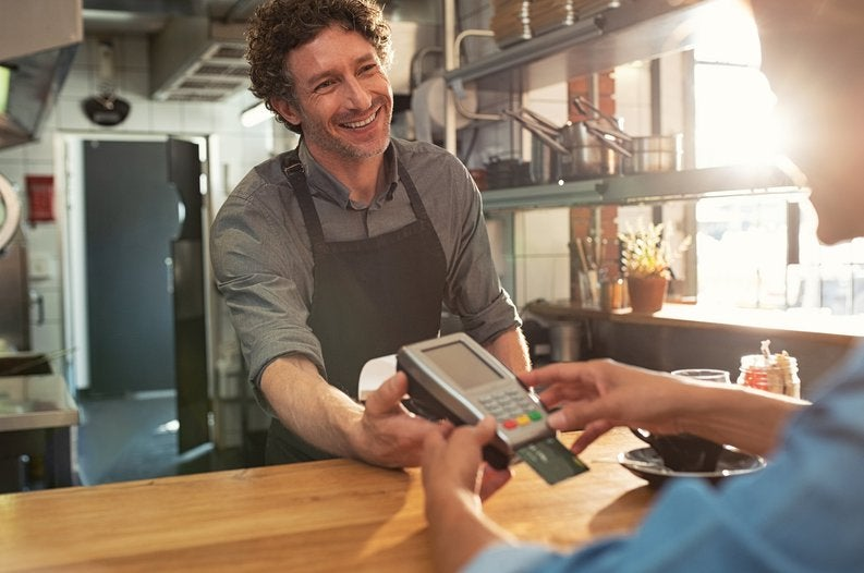 A cafe employee holding a credit card reader while the customer enters their PIN.