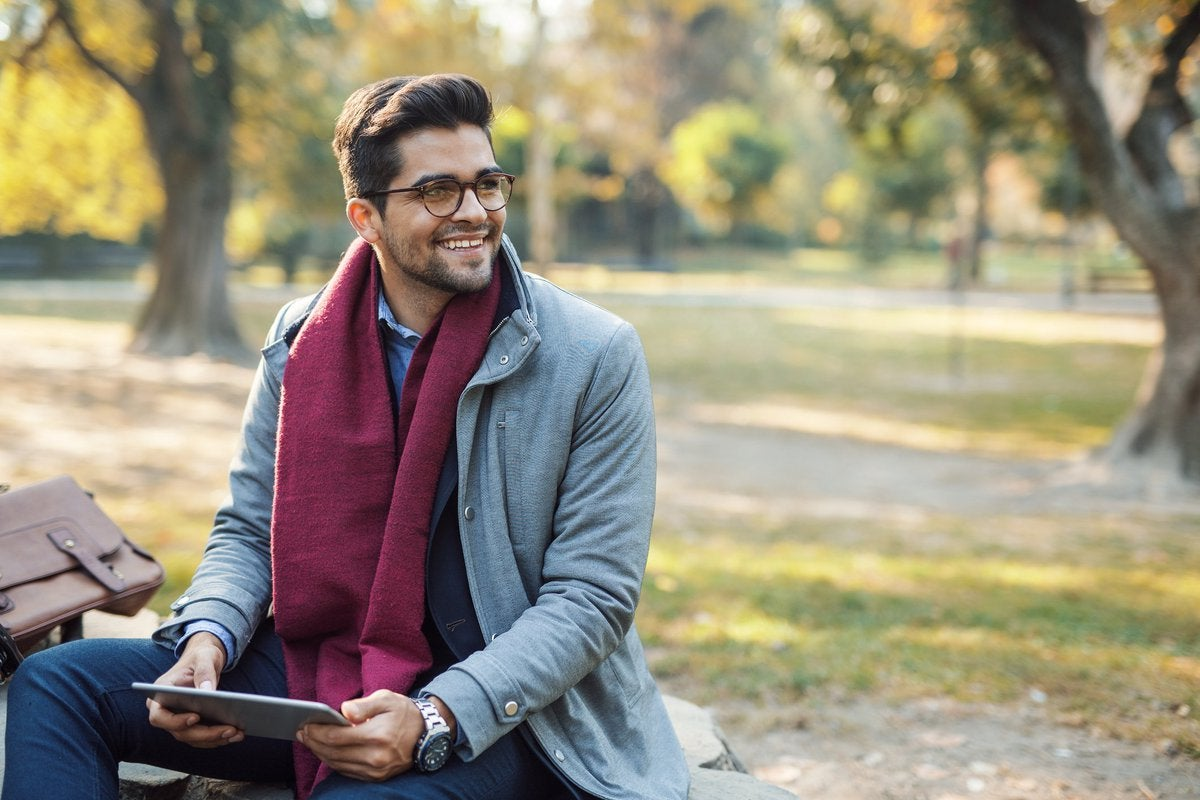 A well-dressed man in a park holding a tablet.