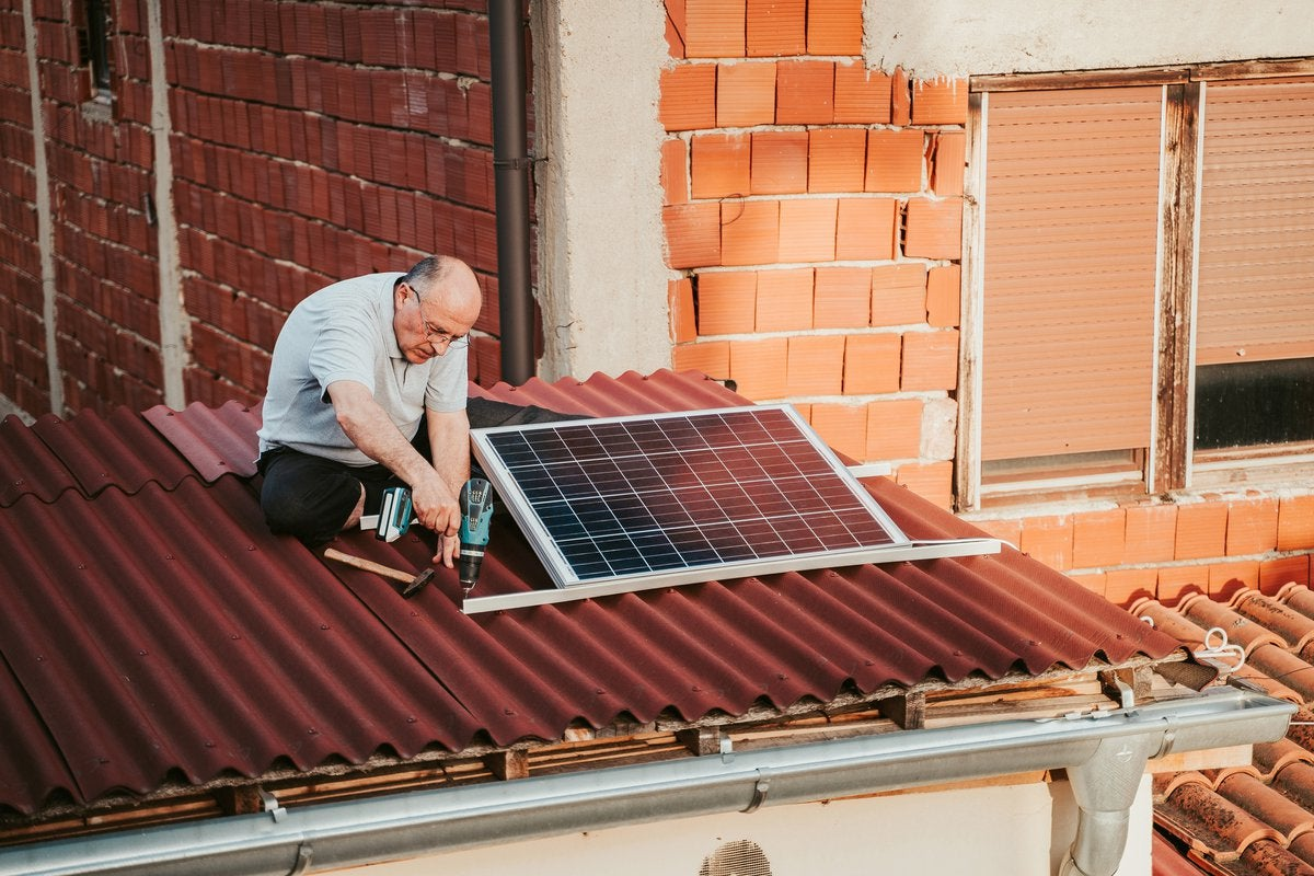 Man installing solar panels on the roof of a home.