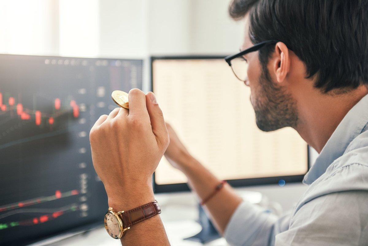Человек смотрит на графики на экране компьютера, держа золотой биткойн.