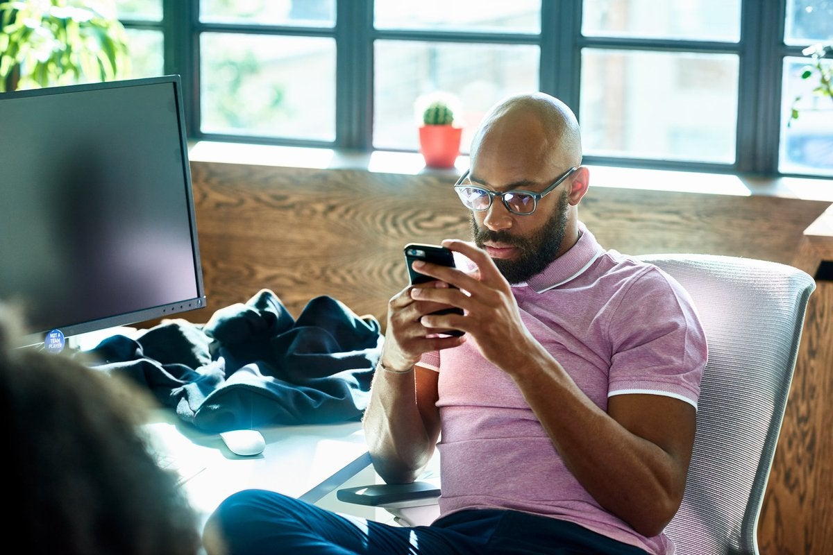A person sitting at an office desk and looking at a cell phone with a contemplative expression.