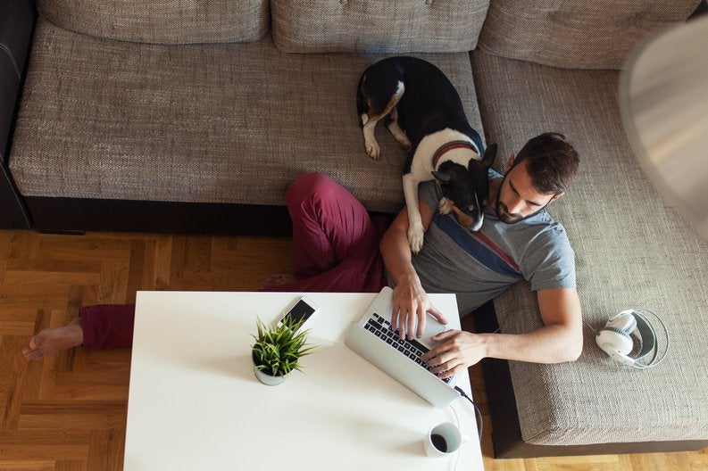 A man on a laptop sitting on the floor next to his couch with his dog's head on his shoulder.