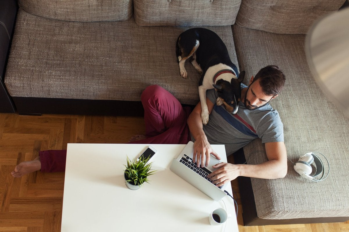 A man sitting on the floor in front of his couch with his dog looking over his shoulder at his open laptop.