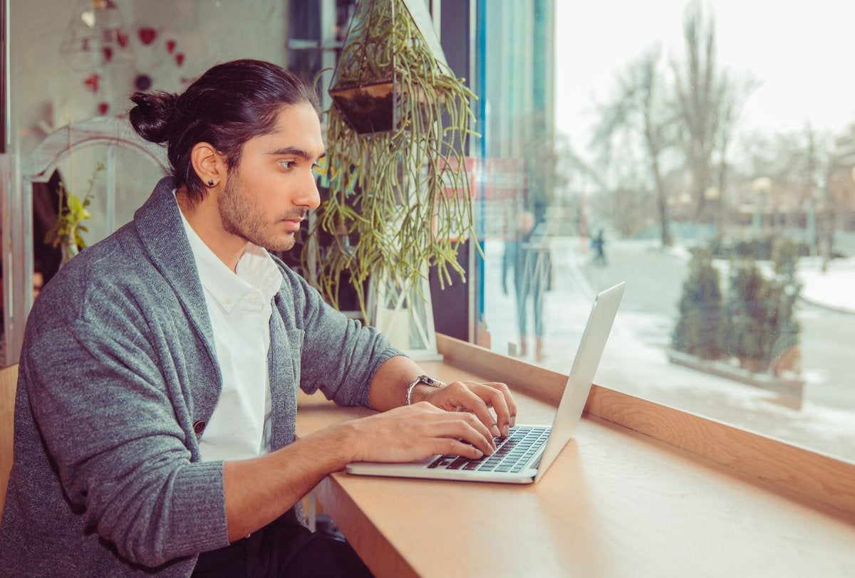 A man working on a laptop while sitting at a window table.