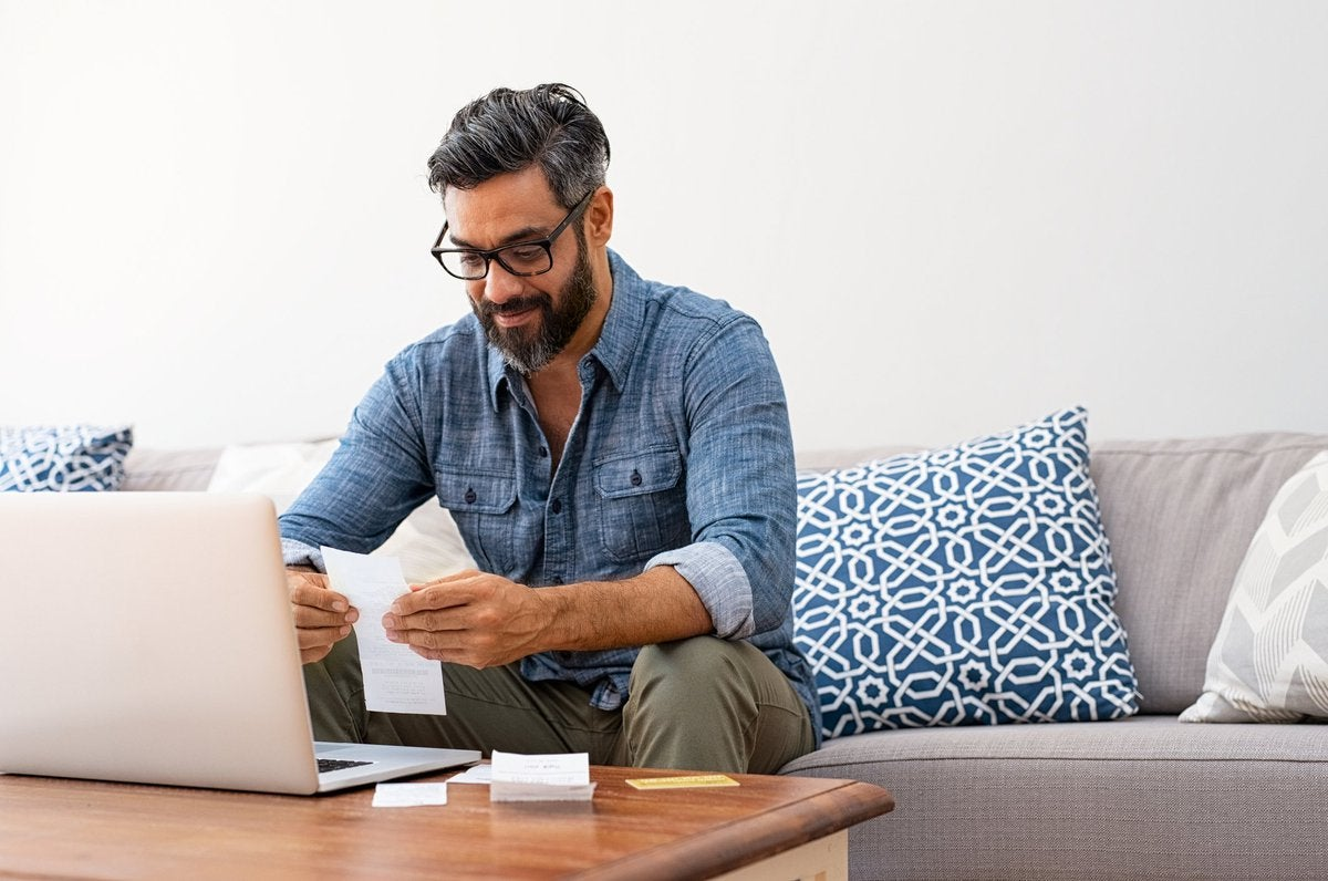A man looking through paper bills while sitting on a couch in front of a laptop.