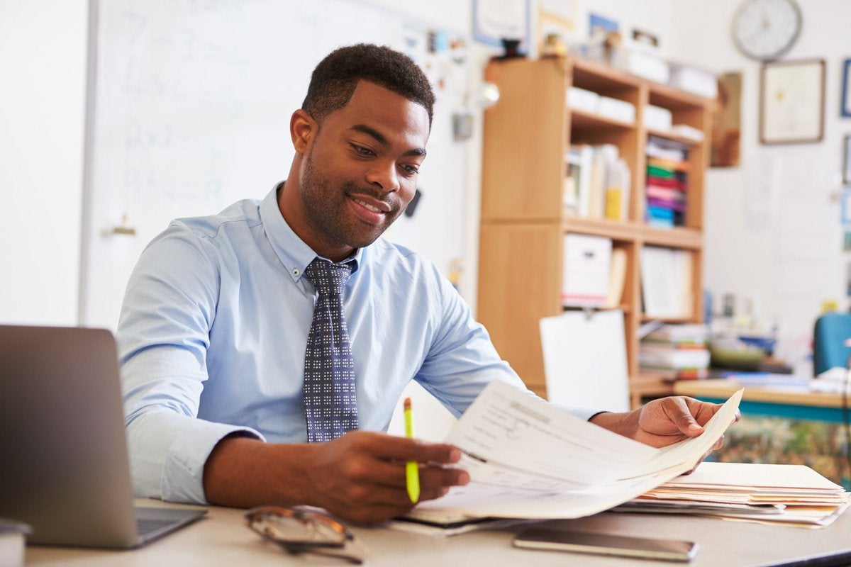 A man reading paperwork at his desk.