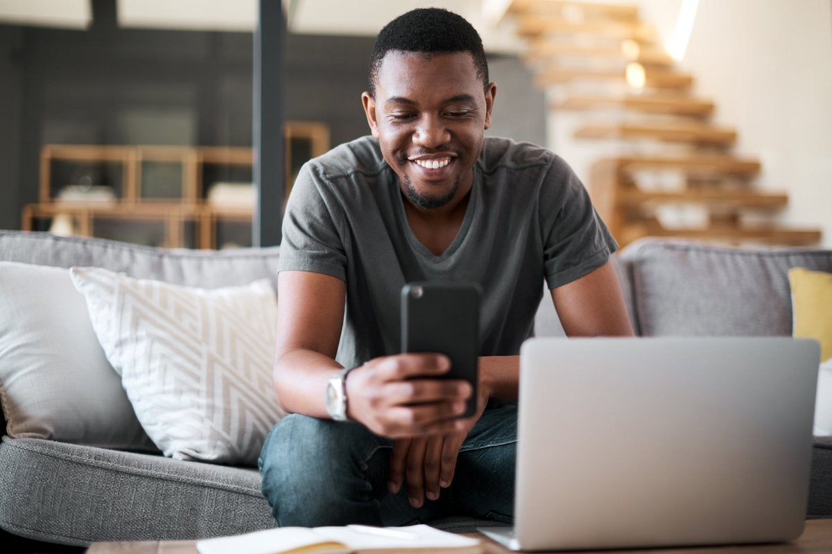 A man sits in his living room, reading the latest crypto news on his phone.