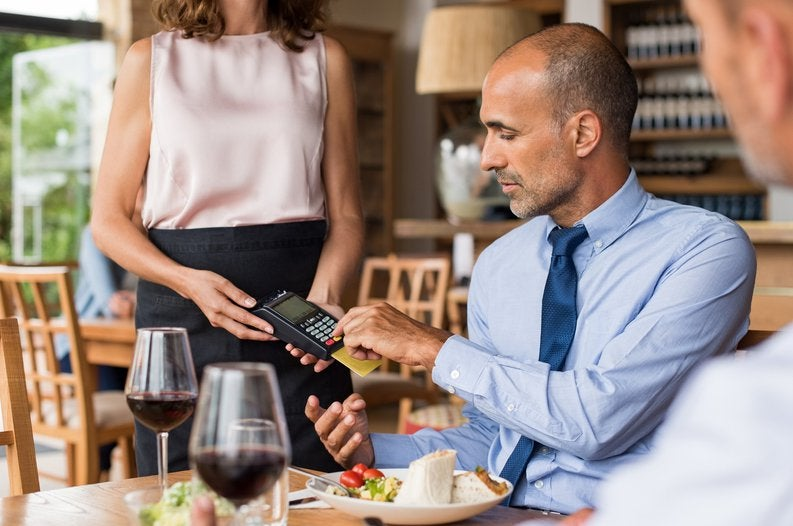 A businessman sitting at a restaurant table and swiping his credit card in the card reader being held by the waitress.