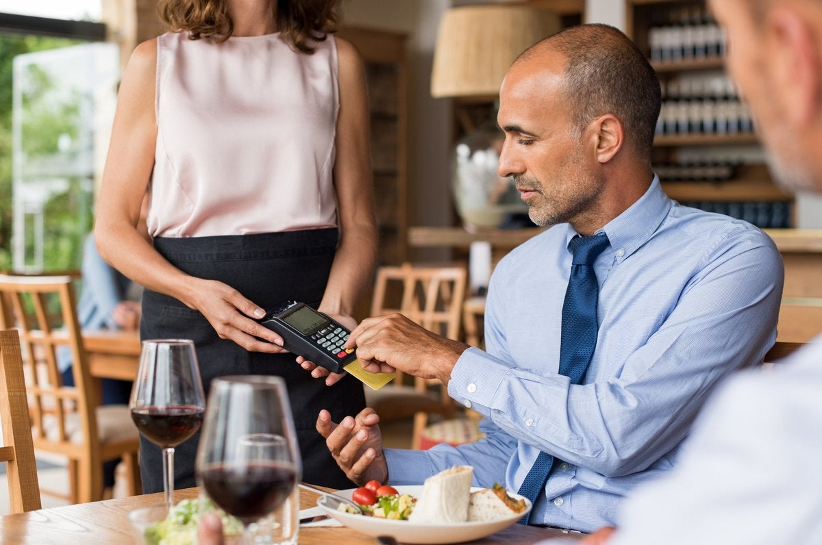 A man sitting in a restaurant swiping his credit card in the card reader being held by a waitress.