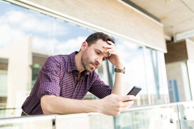 A man looking upset and leaning against a balcony railing while looking at his phone with his head resting in one hand.