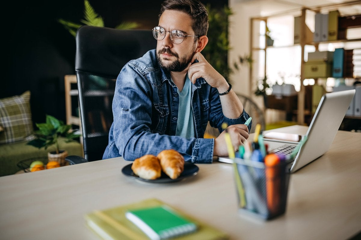 Man with glasses using laptop looks away appearing to be in thought.