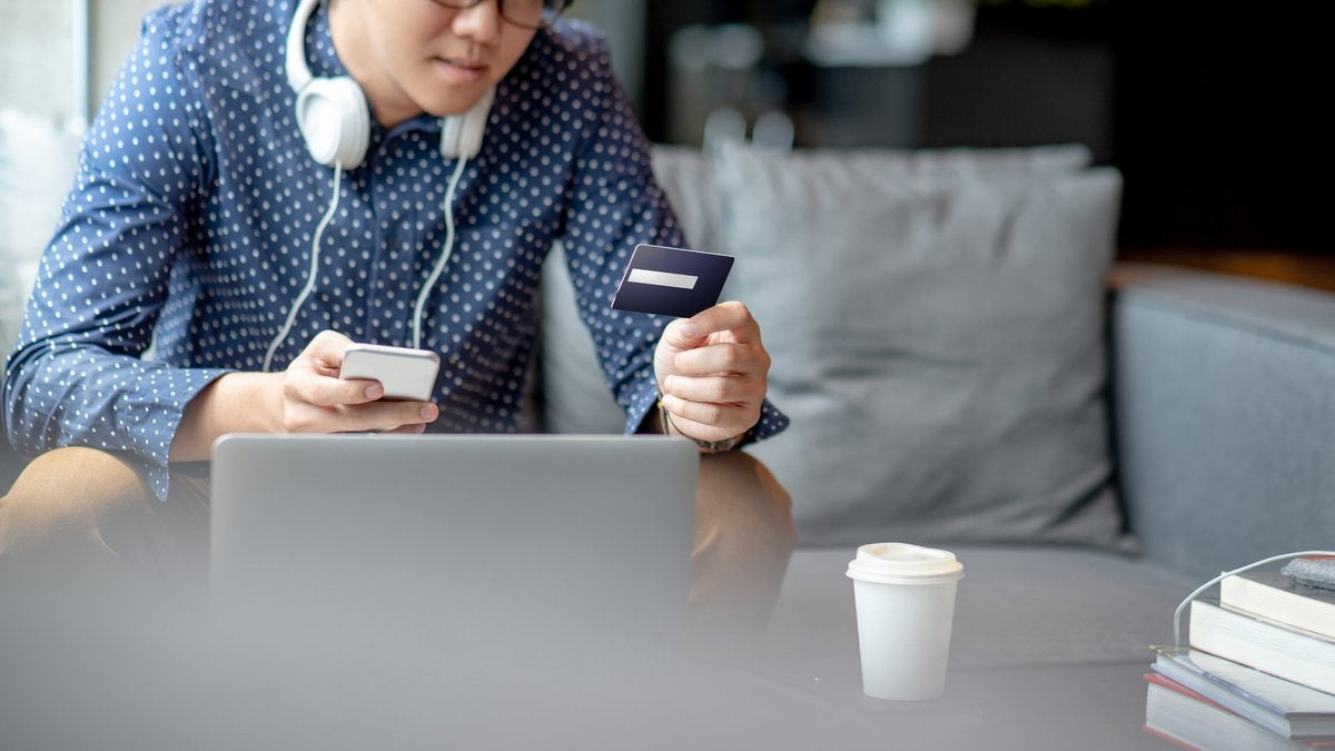 A man sitting on his couch in front of a laptop while holding his phone and a credit card.