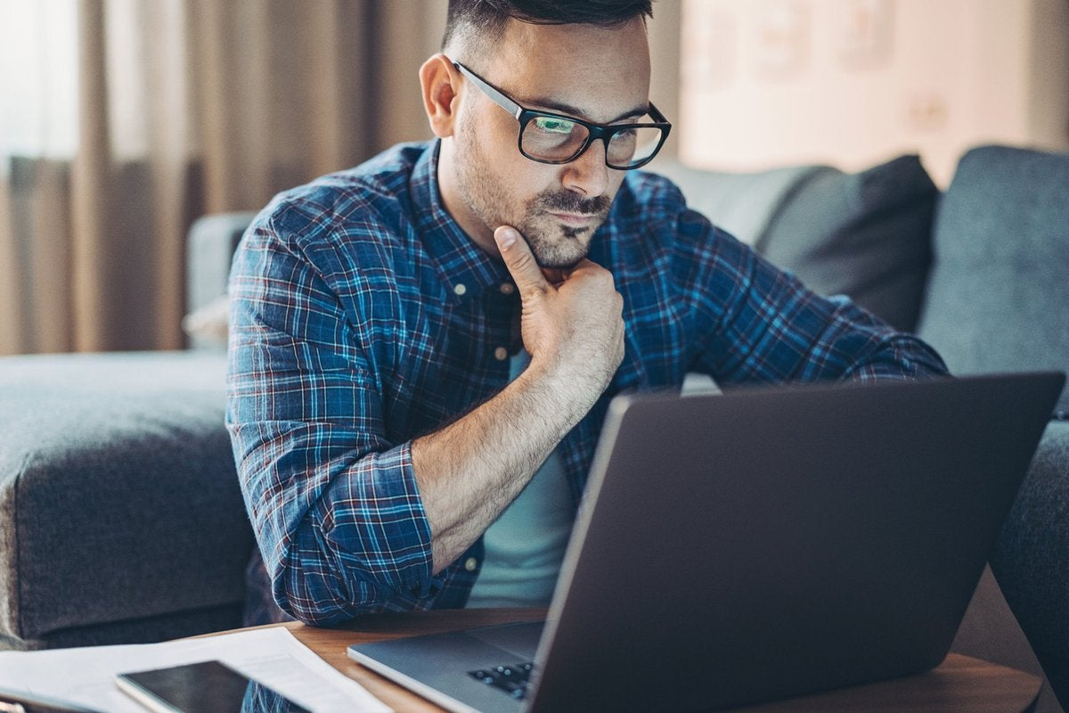 Man with glasses looking at laptop.